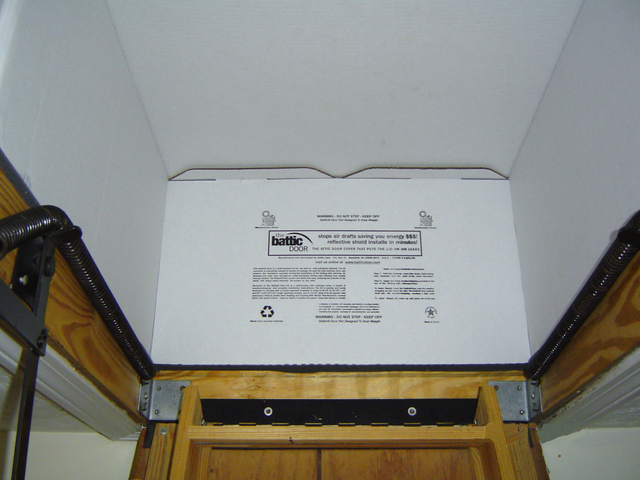 ... photo - This close-up view of the cardboard box shows how well it seals again the the attic floor to block air leakage. - Photo credit - Battic Door & Dulley Column - Color graphics